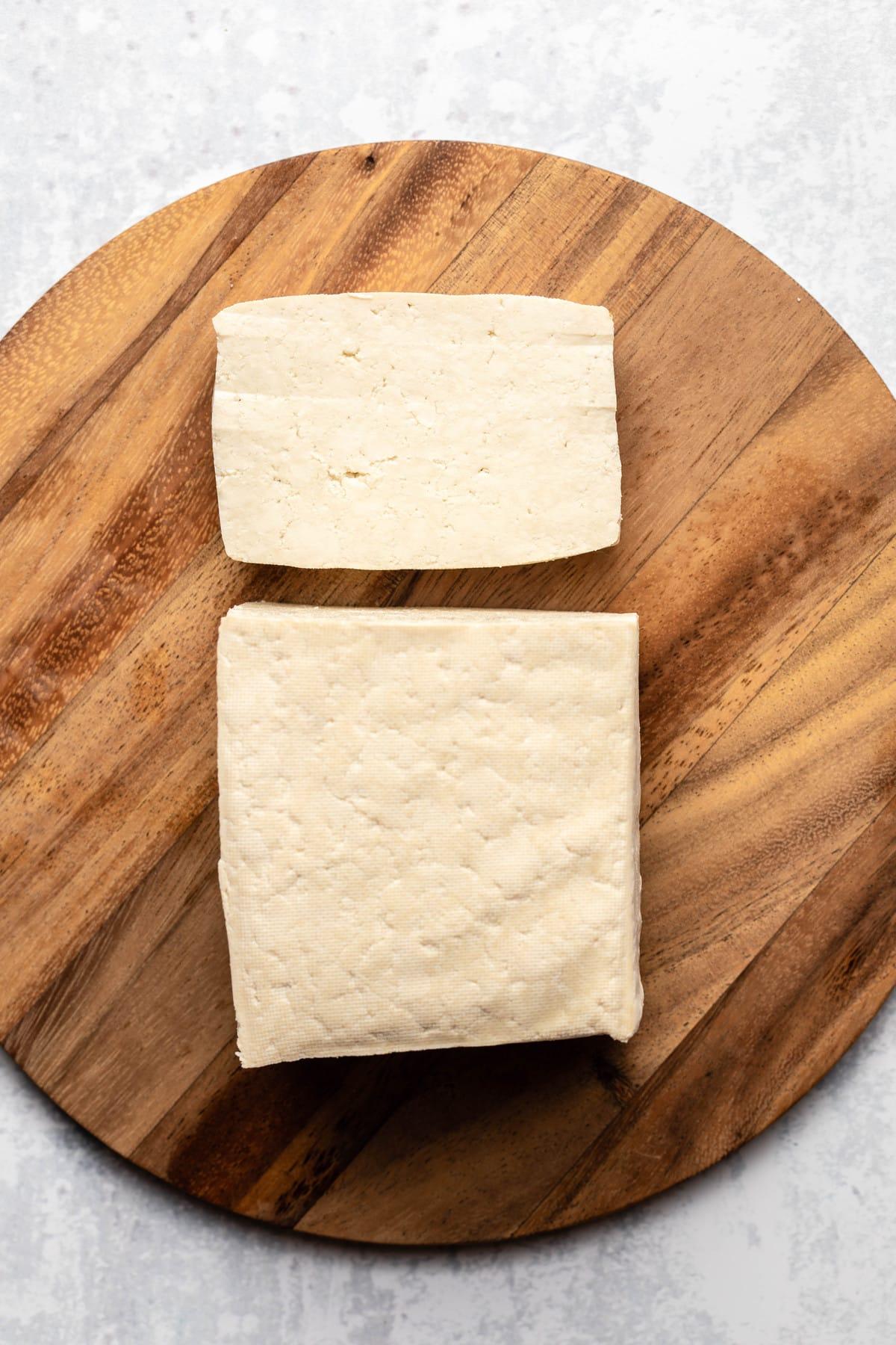 block of super firm tofu on round wood cutting board