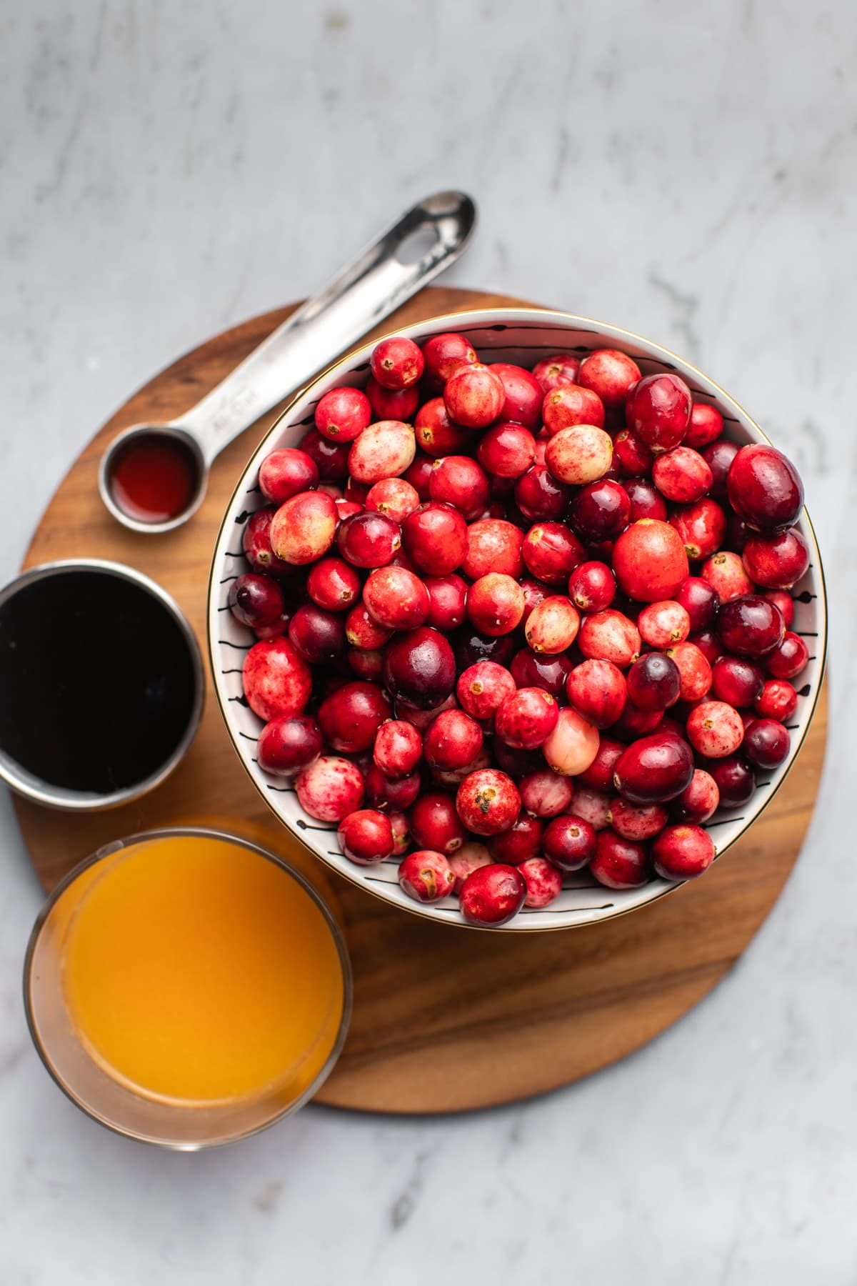 ingredients for cranberry sauce in small bowls on wooden cutting board