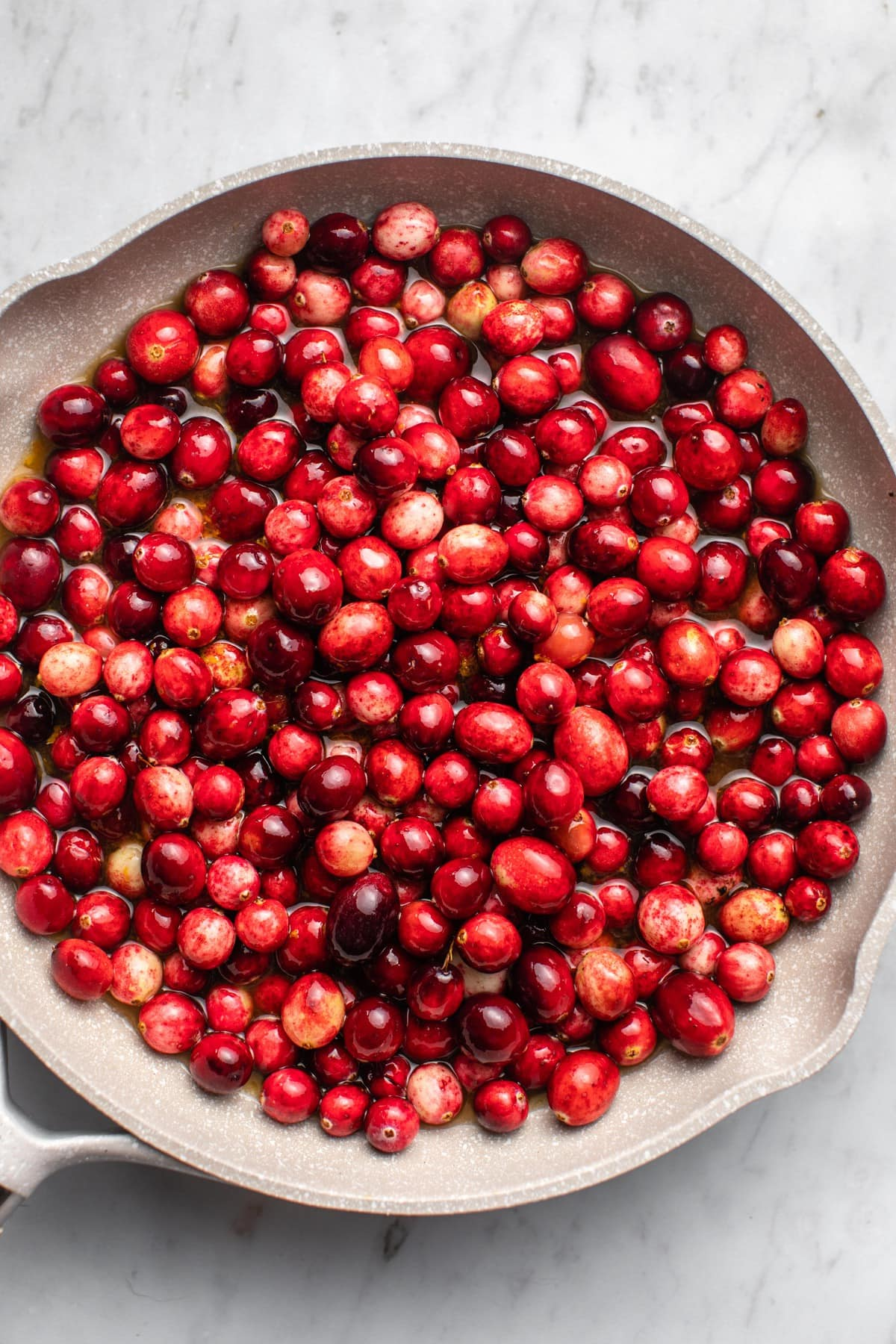 cranberry sauce ingredients mixed together in a grey saucepan before cooking