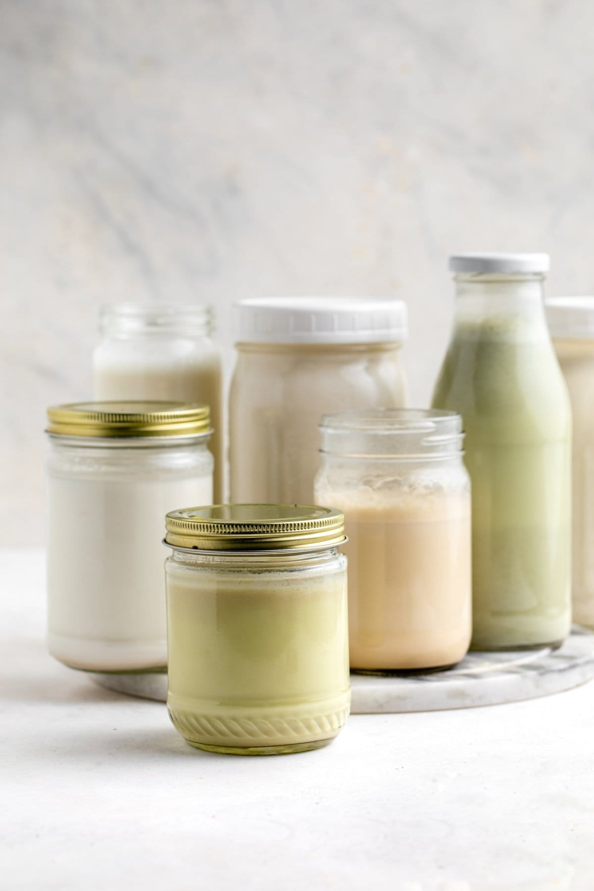 homemade nut milks in different sized glass jars on white background