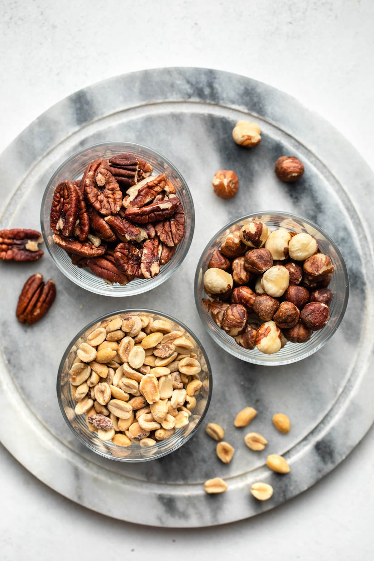glass bowls of pecans, hazelnuts, and peanuts