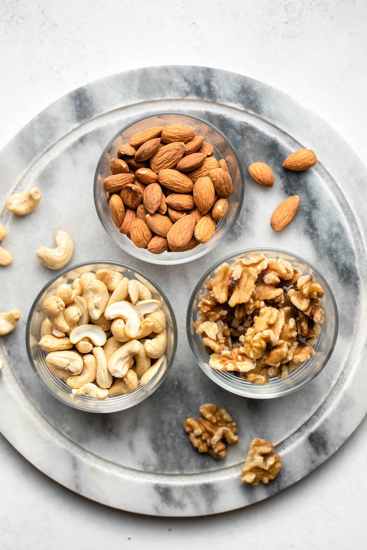 glass bowls of almonds, walnuts, and cashews