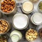 glass jars of nuts, seeds, and homemade nut milks on marble background