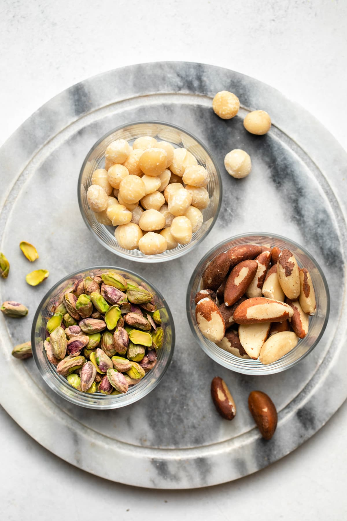 glass bowls of macadamia nuts, pistachios, and brazil nuts