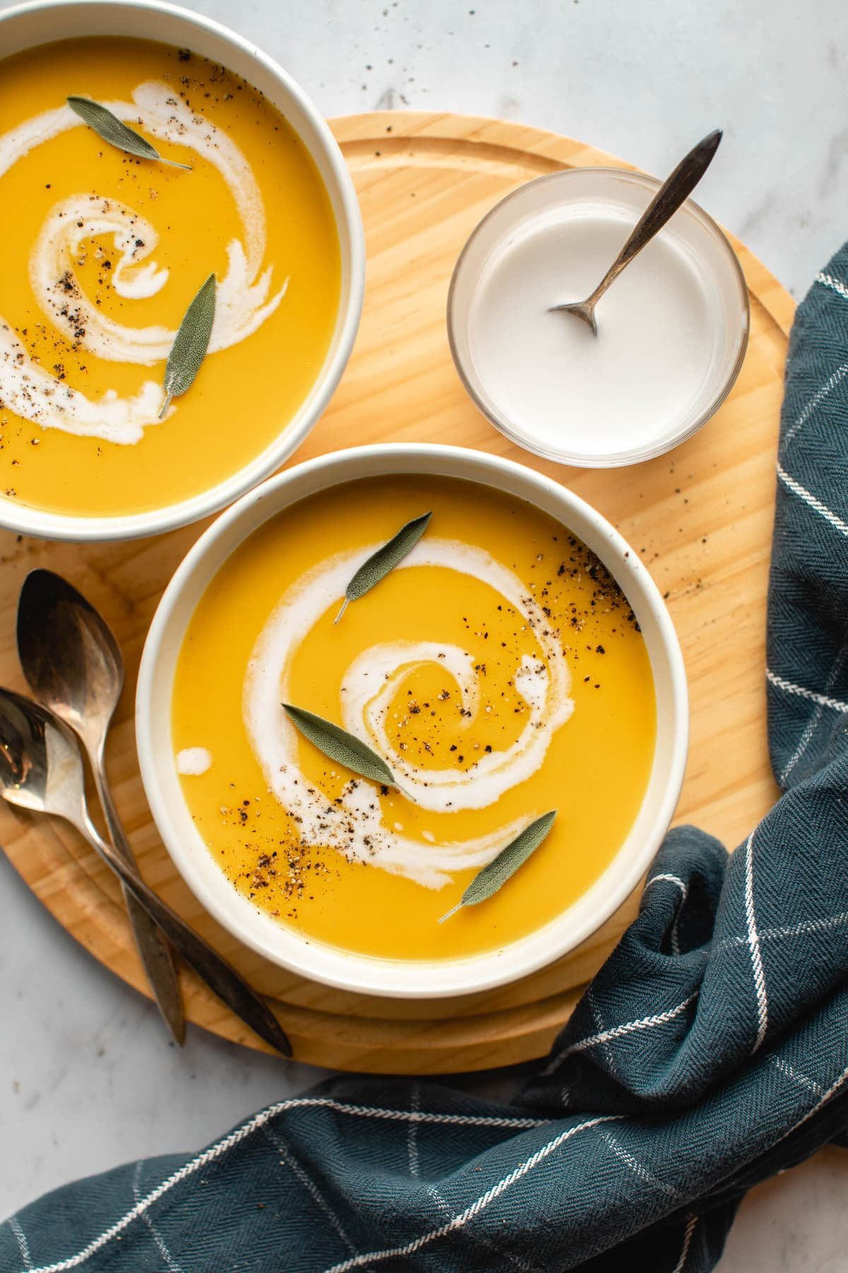 two bowls of butternut squash and apple soup in white bowl on wooden cutting board with marble background