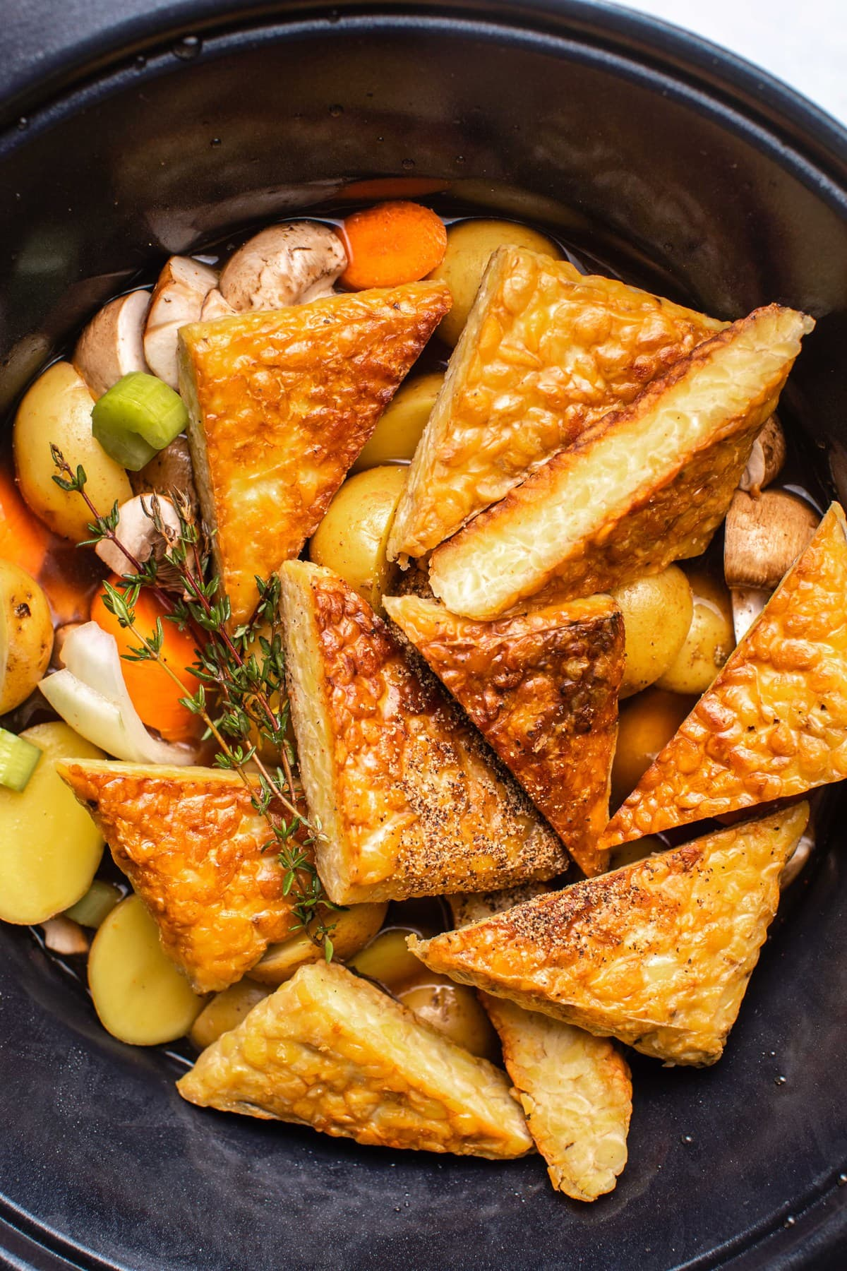 close up picture of tempeh and vegetables for pot roast in slow cooker before cooking