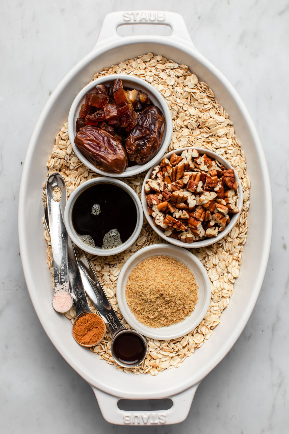 ingredients for maple pecan oatmeal in small white dishes in larger white dish on marble background