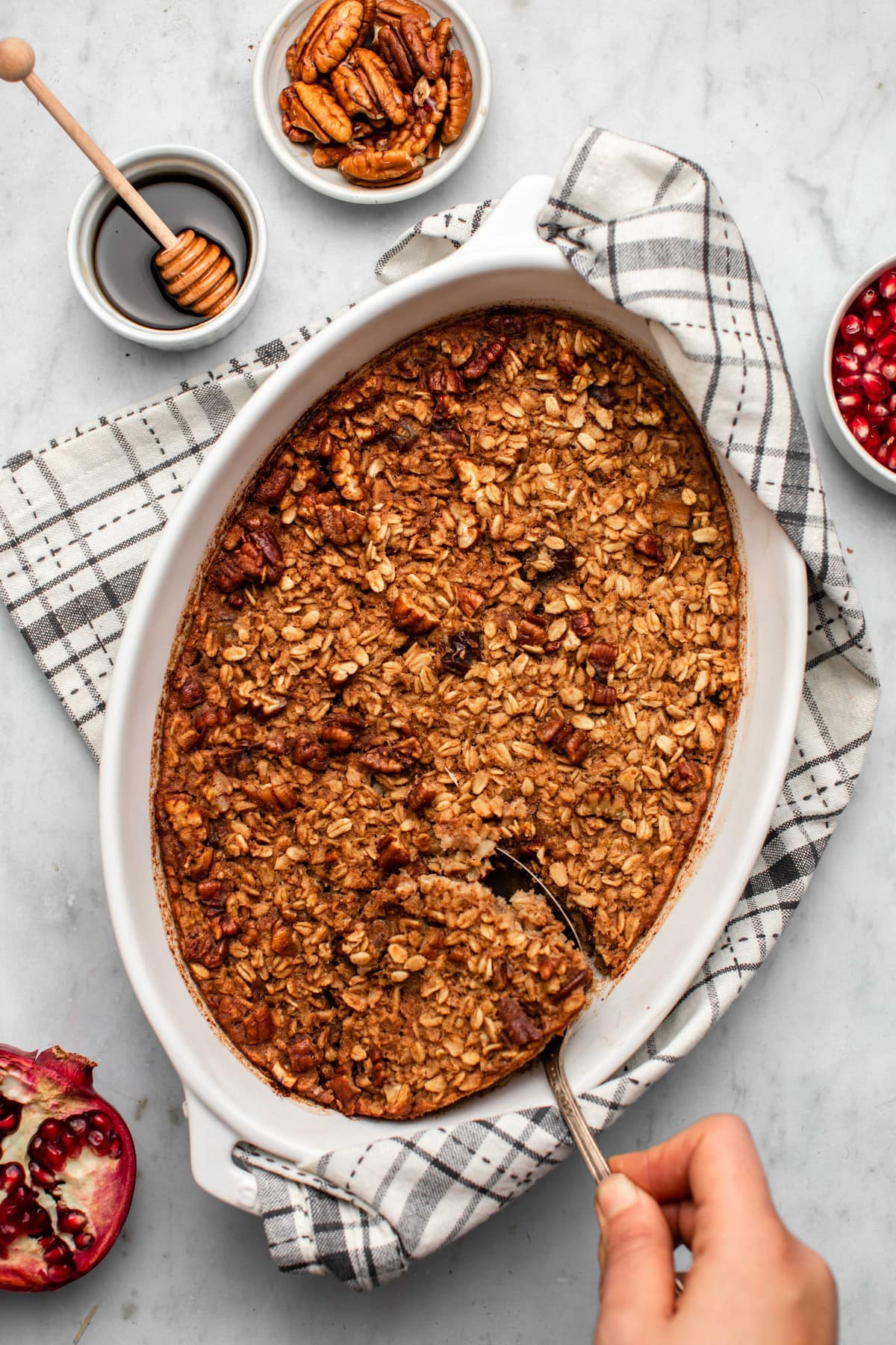 hand scooping out baked vegan maple pecan oatmeal on marble background