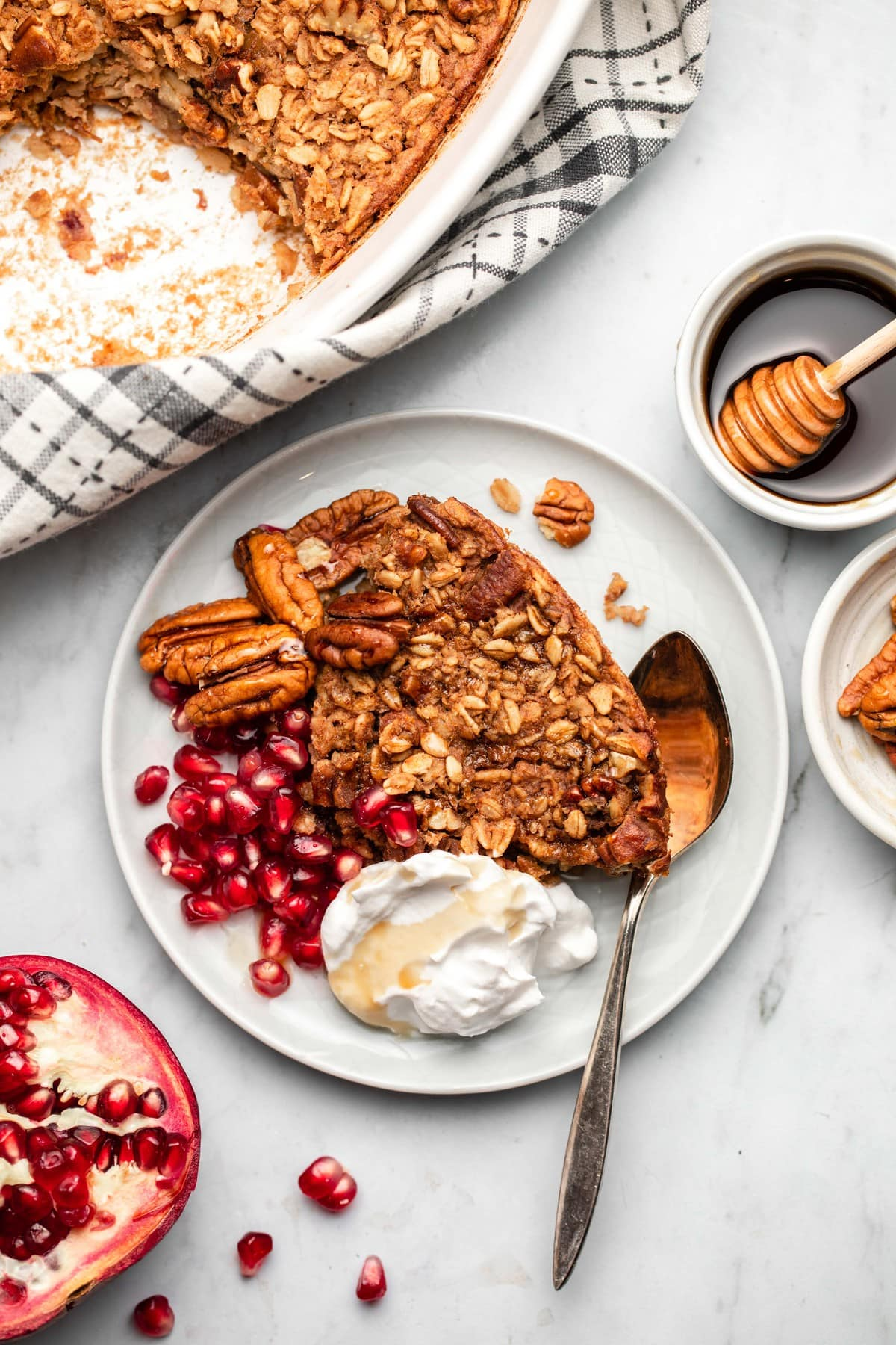 plate of maple pecan baked oatmeal decorated with pecans, pomegranate, seeds, coconut yogurt, and maple syrup on marble background