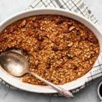 baked maple pecan oatmeal in round white casserole dish with large serving spoon on marble background