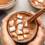 two hands holding glass mug of hot cocoa with marshmallows and cinnamon stick