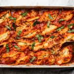 vegan stuffed shells with red sauce and basil in white baking dish on marble background