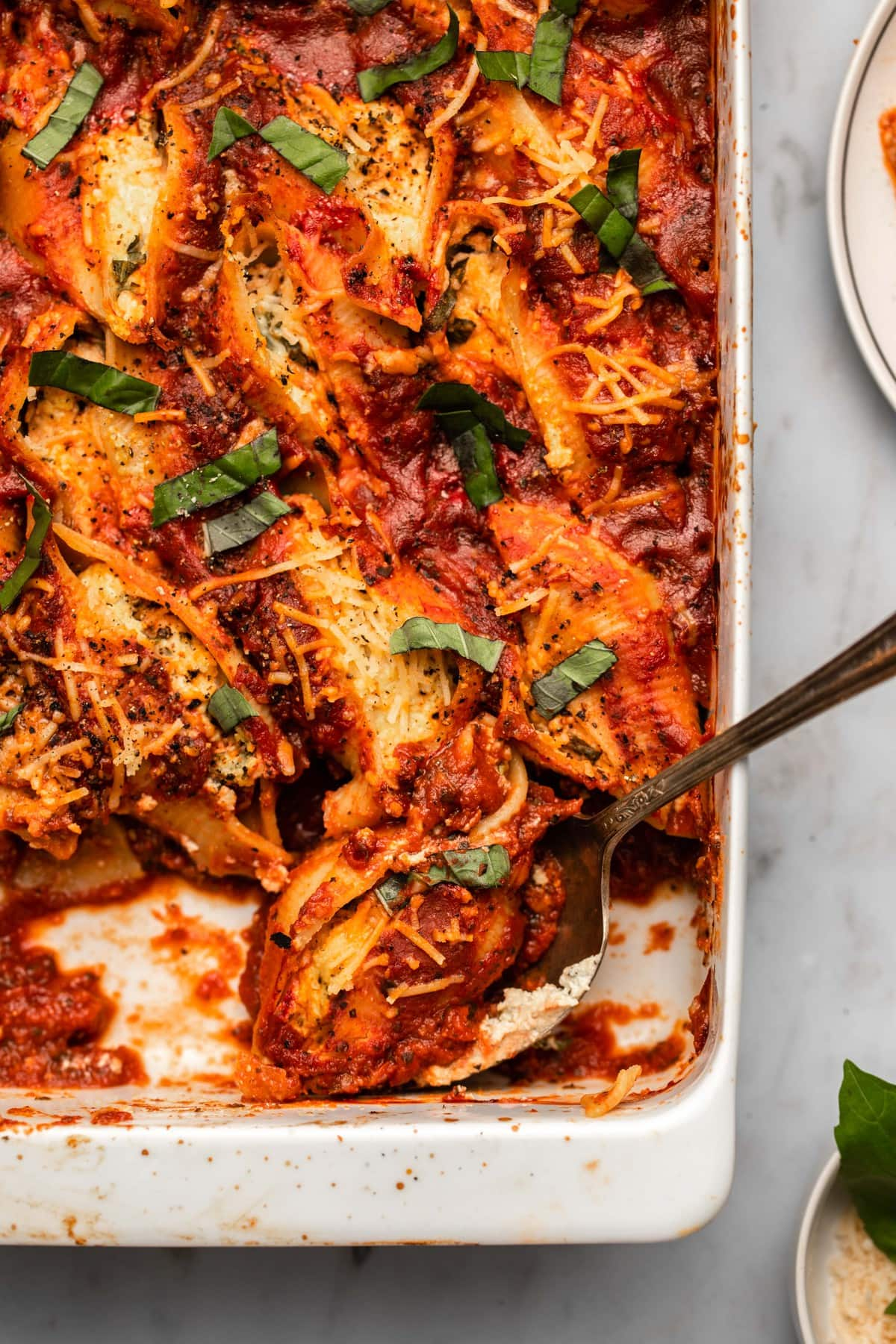 vegan stuffed shells topped with fresh basil in white casserole dish with metal serving spoon
