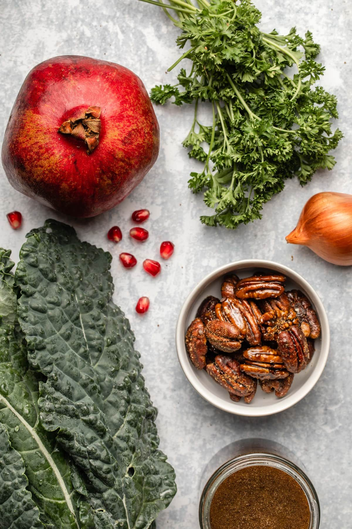 ingredients for kale salad on blue textured background