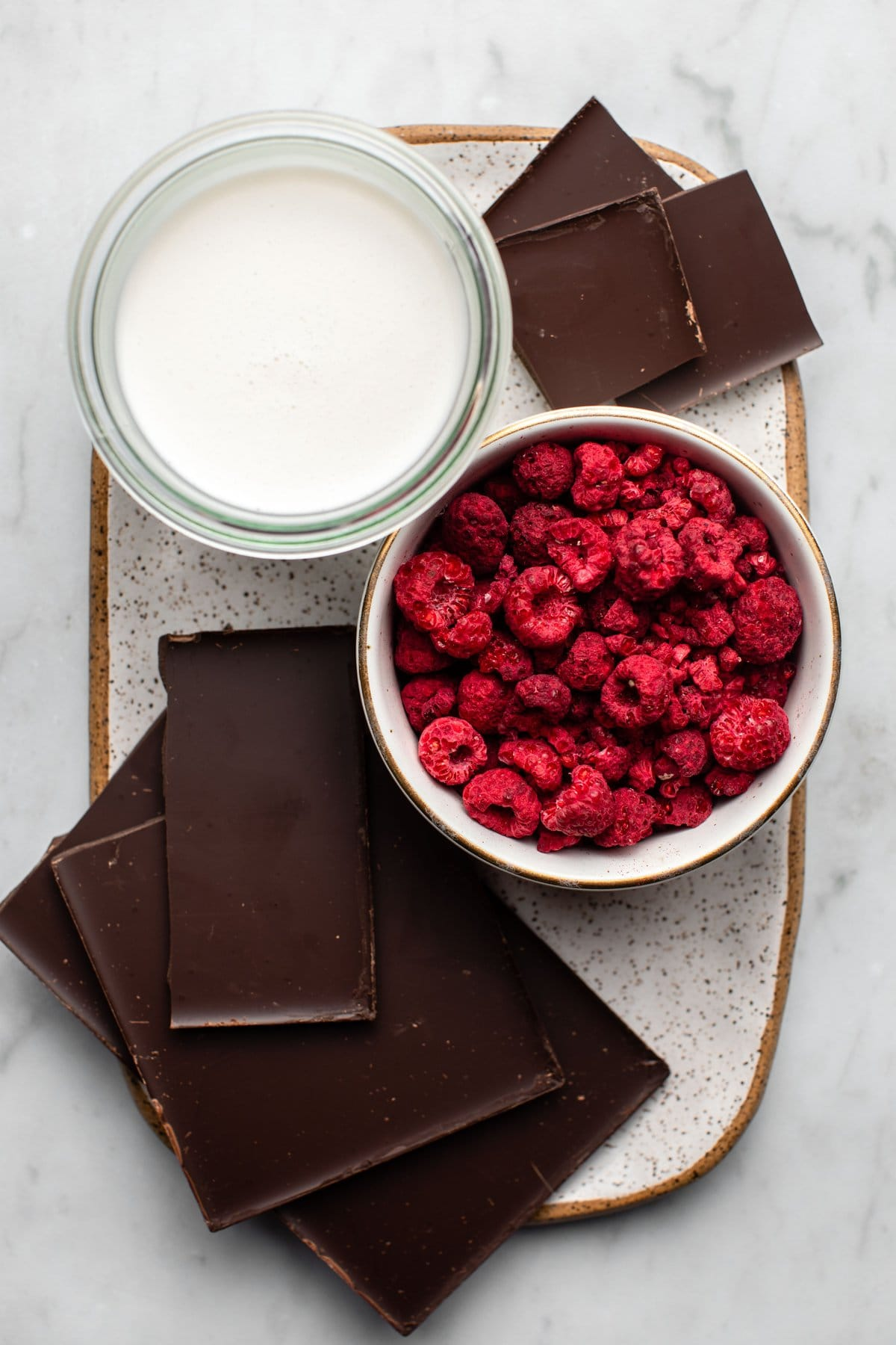 ingredients for chocolate raspberry truffles on white speckled ceramic tray