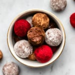 bowl of chocolate raspberry truffles coated in various powders on marble background