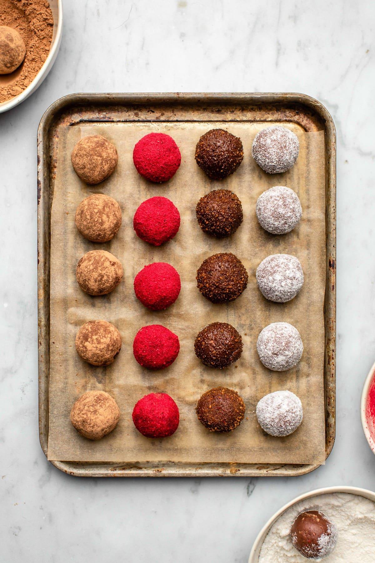 vegan chocolate truffles coated in cacao powder, raspberry powder, coconut sugar, and coconut milk powder on lined baking tray