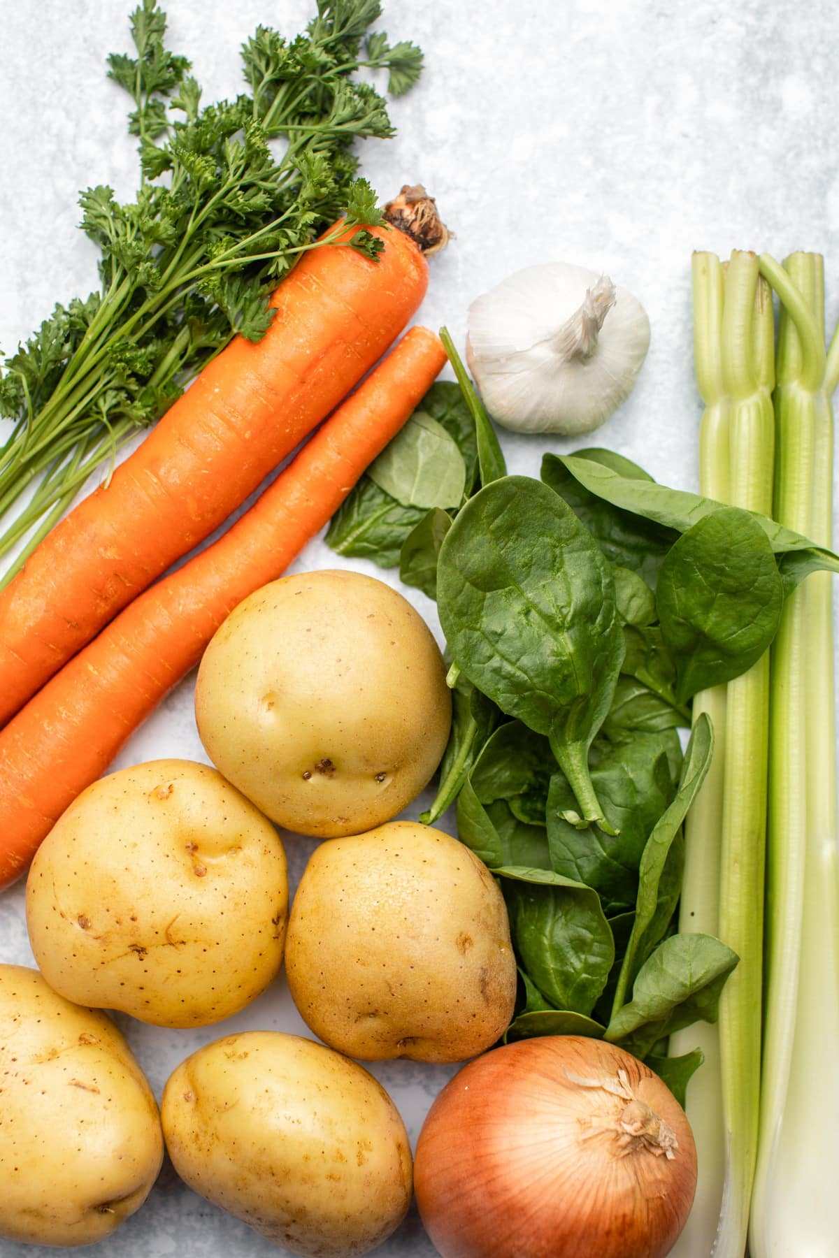 vegetable ingredients for potato spinach soup on marble background