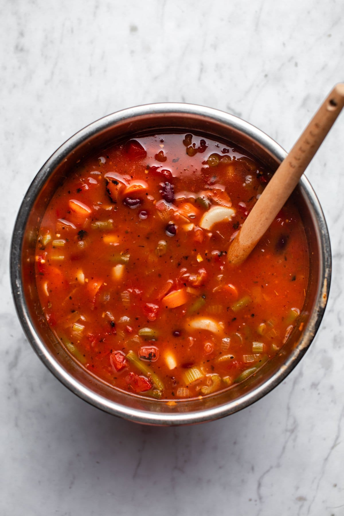 instant pot base filled with cooked minestrone soup on marble background