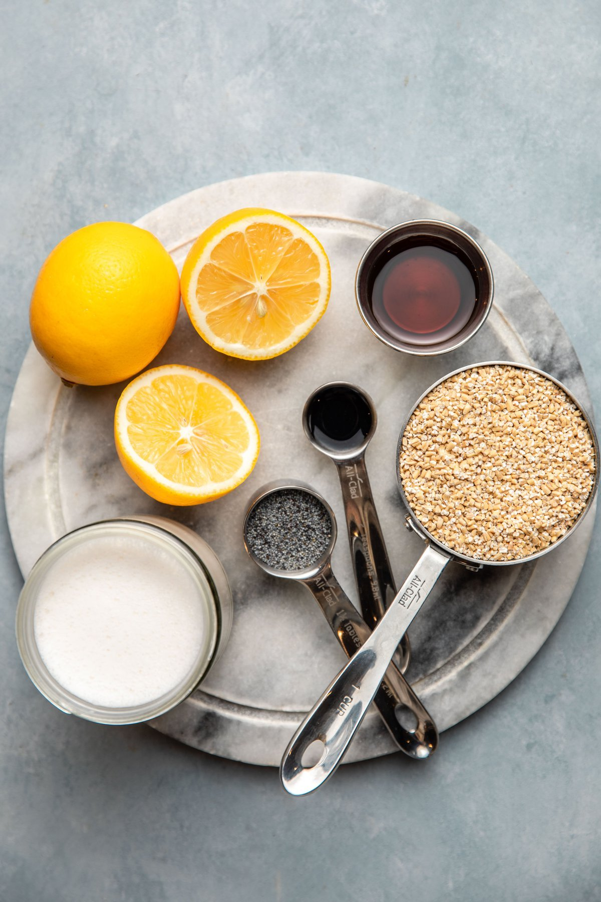 ingredients for lemon poppyseed oatmeal in measuring cups on round marble cutting board