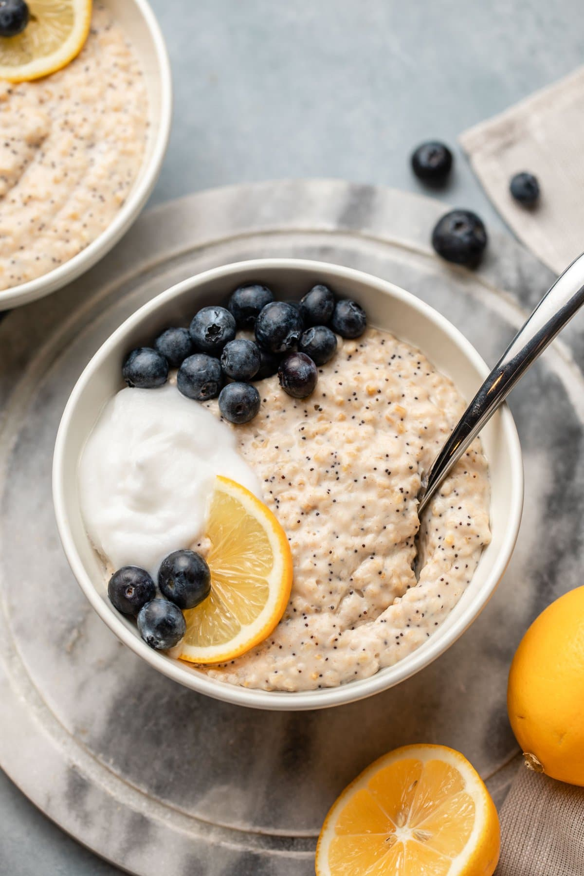 lemon poppyseed oatmeal topped with coconut yogurt and blueberries in white bowl on marble background