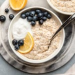 lemon poppyseed oatmeal in white bowl on marble background surrounded by lemons and blueberries