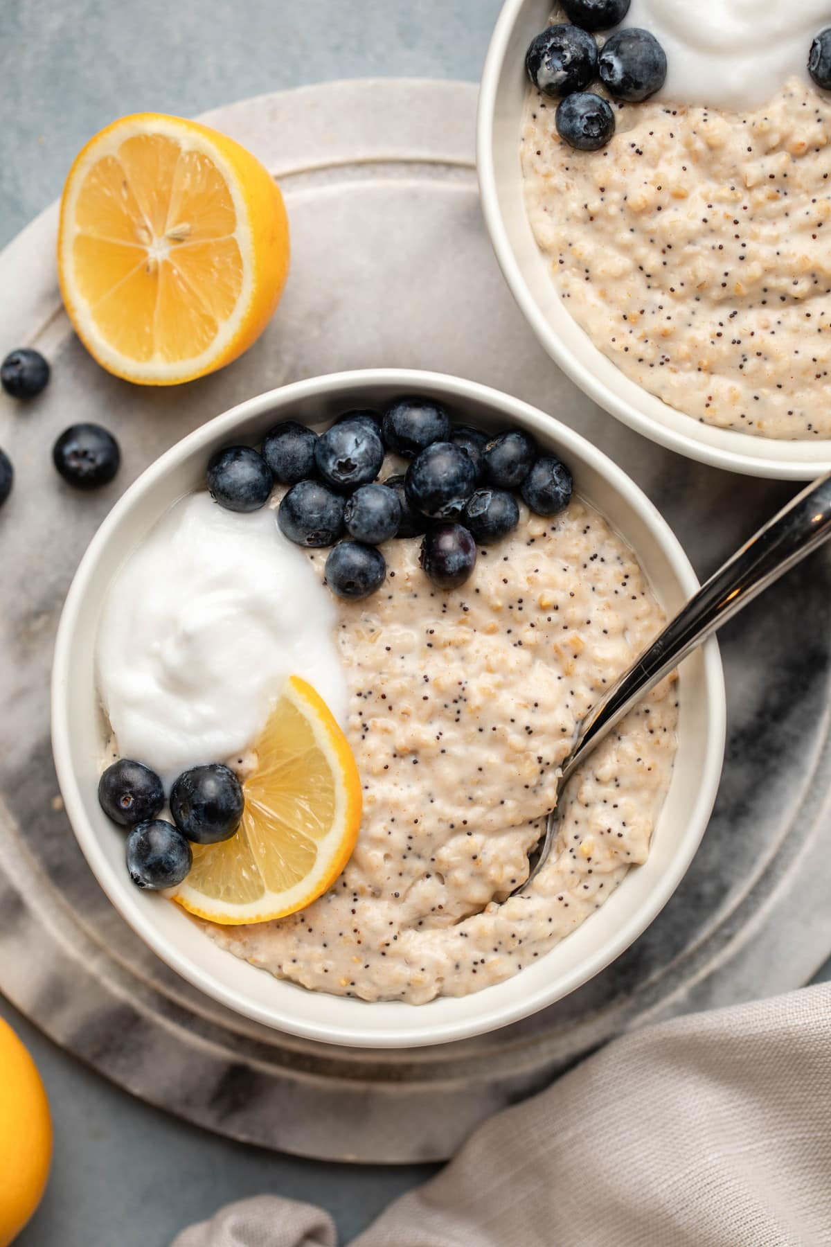 lemon poppyseed oatmeal with blueberries and coconut yogurt in white bowl on marble background