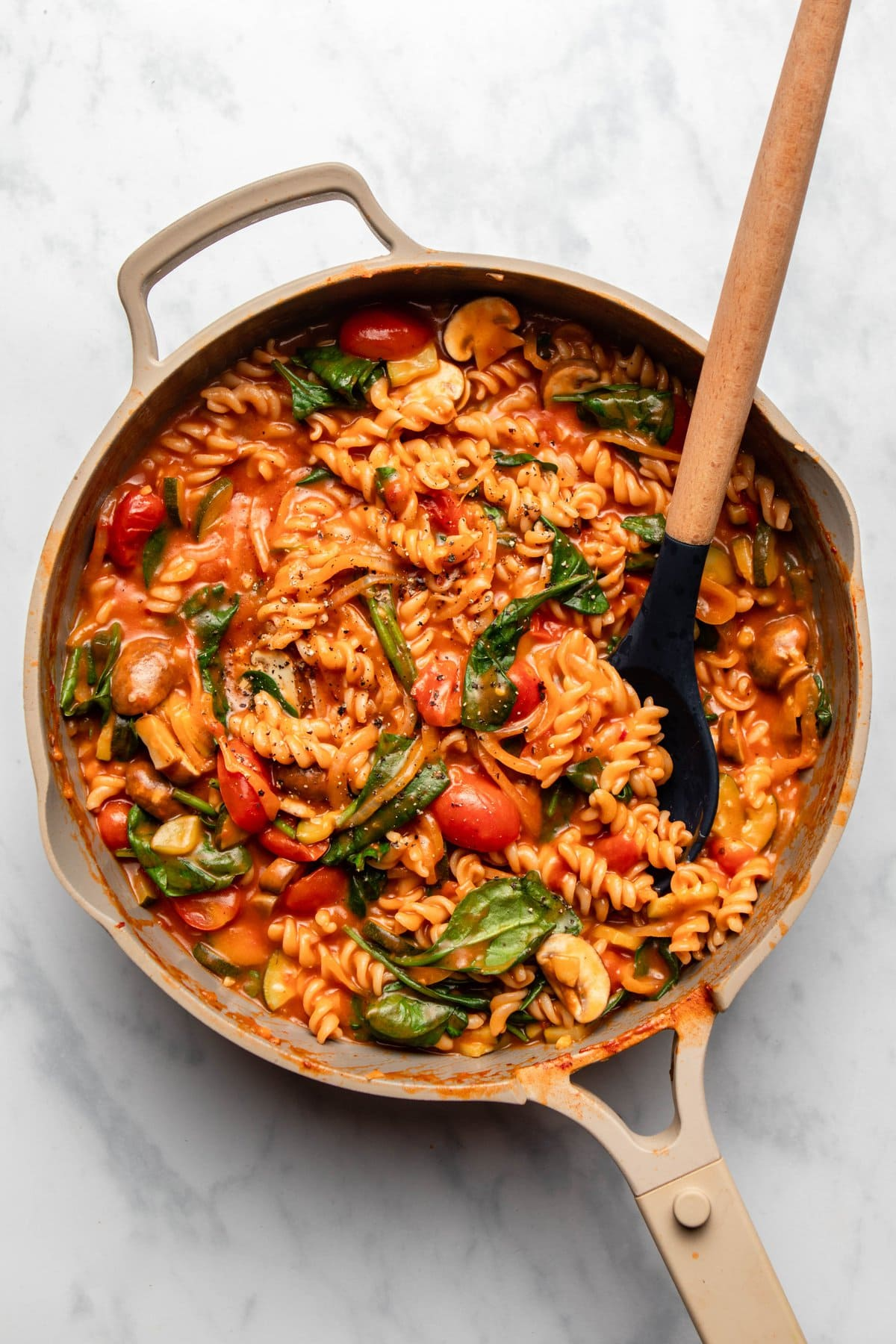 pan of cooked one pot pasta with red sauce on marble background