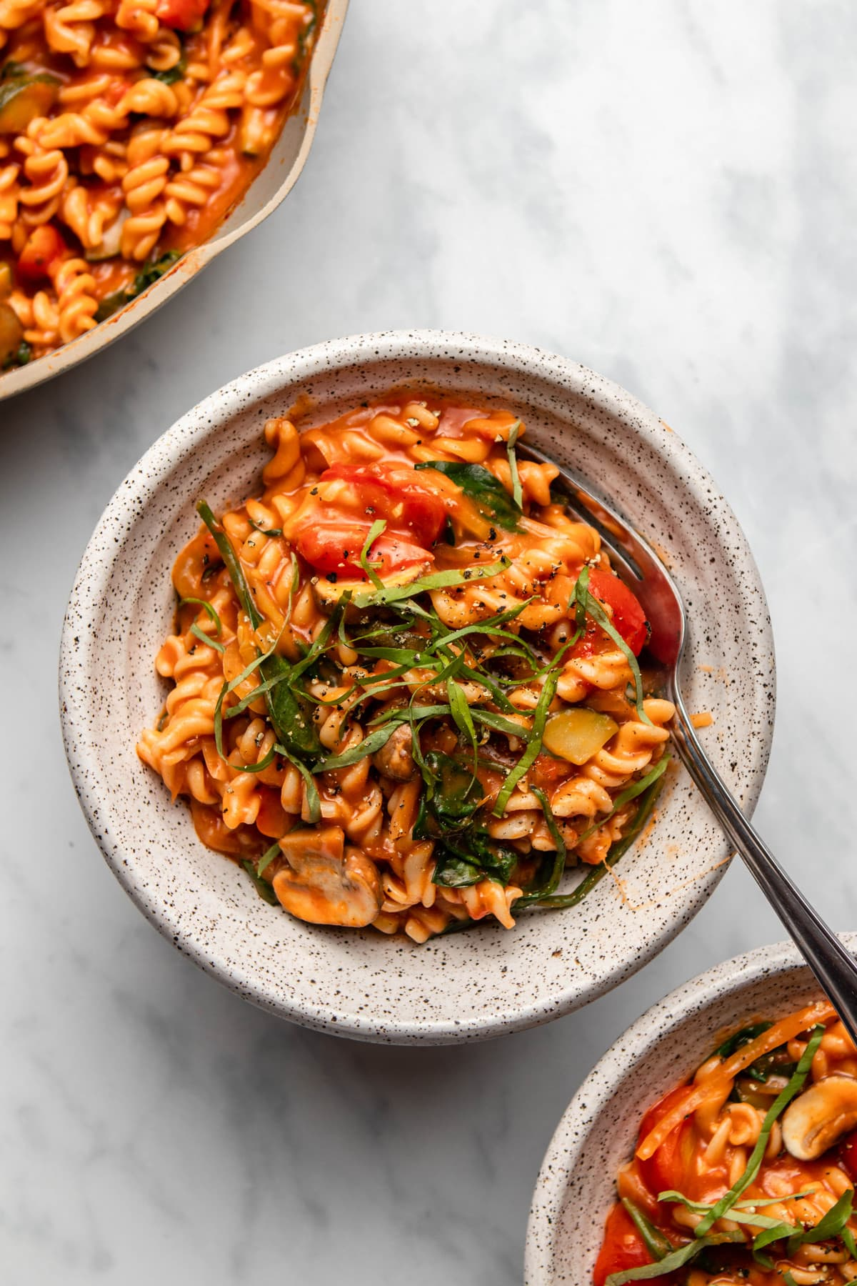 bowl of cooked one pot pasta next to pan of pasta on marble background