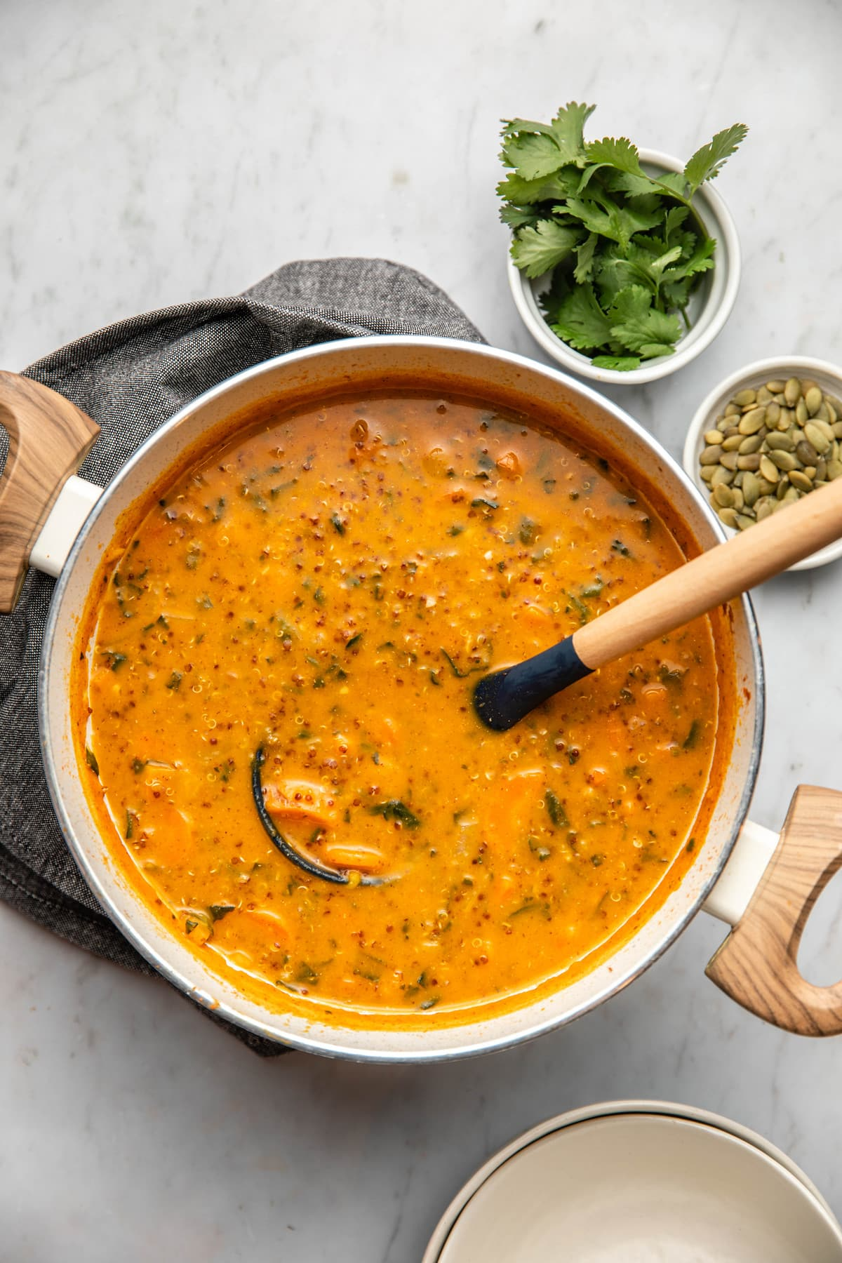 pot of smoky sweet potato soup on white background with bowls of pumpkin seeds and cilantro