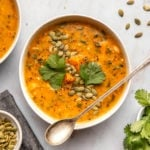 white bowl of smoky sweet potato soup topped with pumpkin seeds and cilantro on marble background