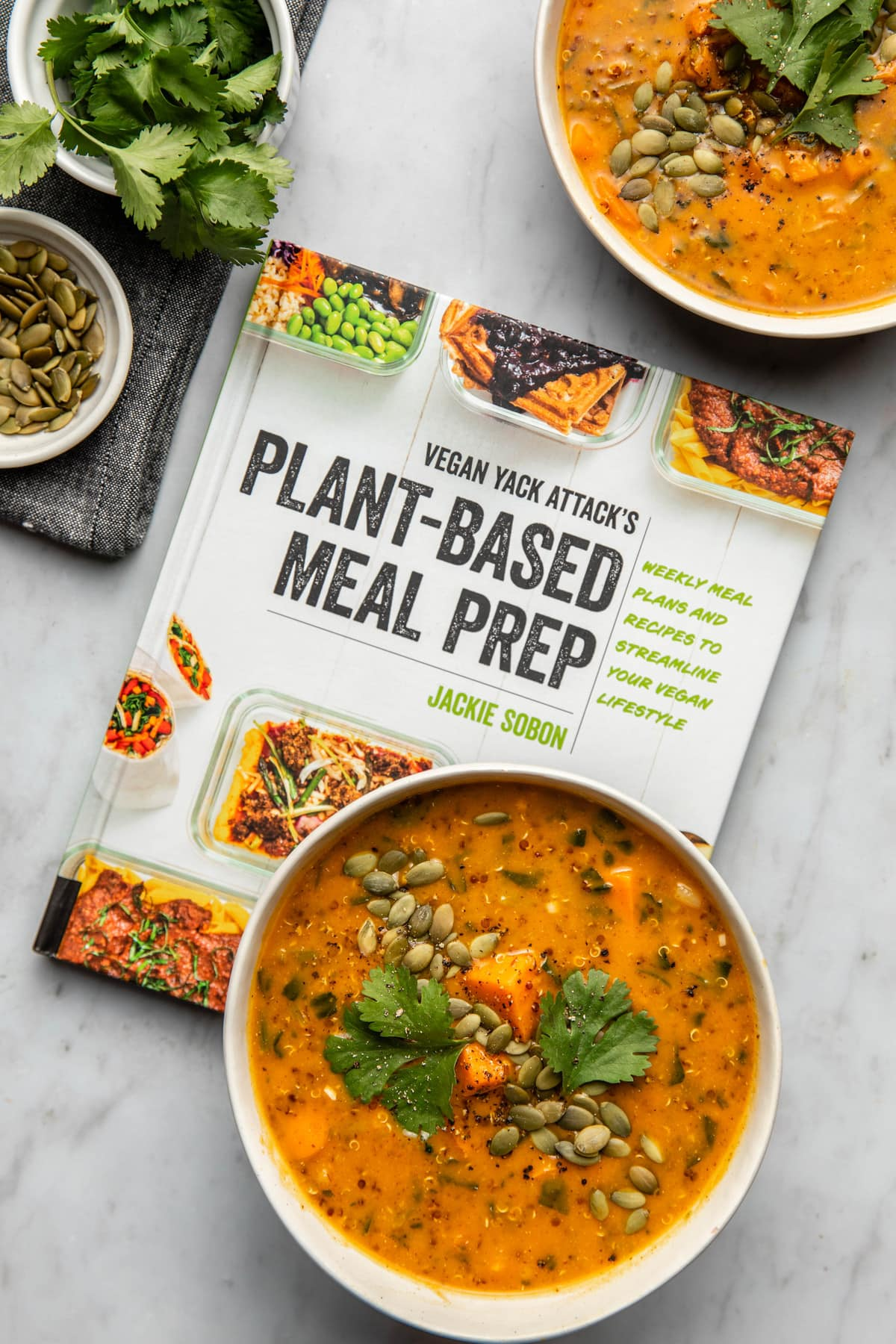 bowl of smoky sweet potato soup on top of plant based meal prep cookbook