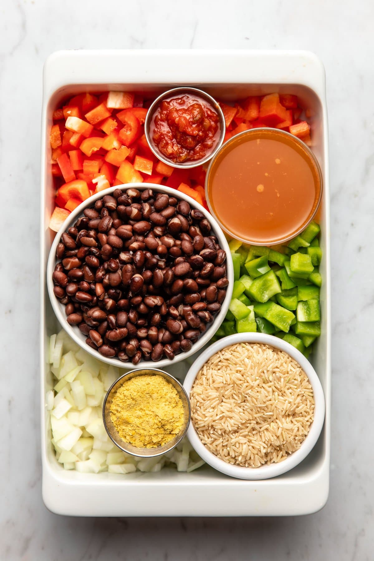 ingredients for southwest black bean casserole arranged in white baking dish