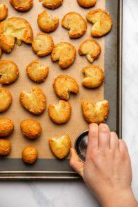 hand smashing potatoes on baking sheet
