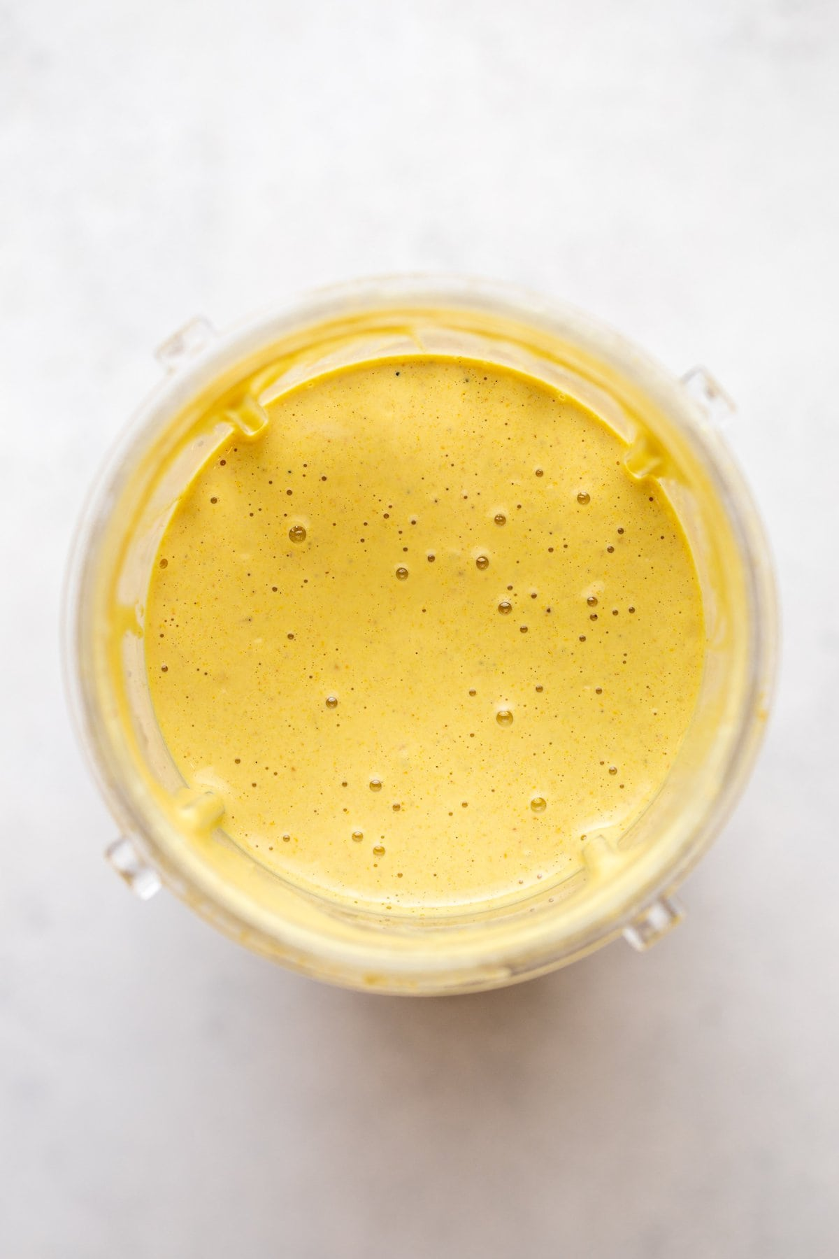 curry tahini dressing blended in bullet blender container on white background