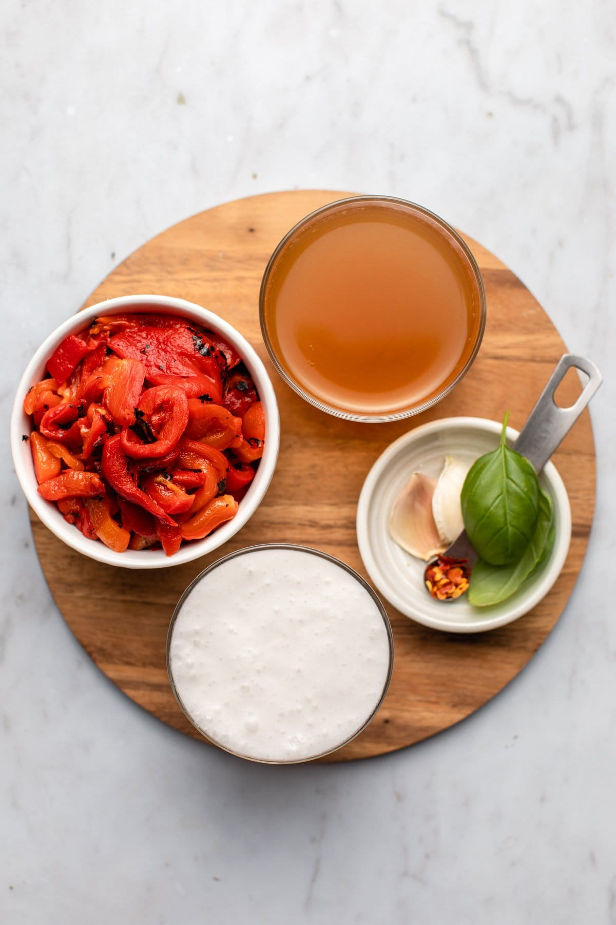 ingredients for red pepper pasta in small glass jars on wooden cutting board