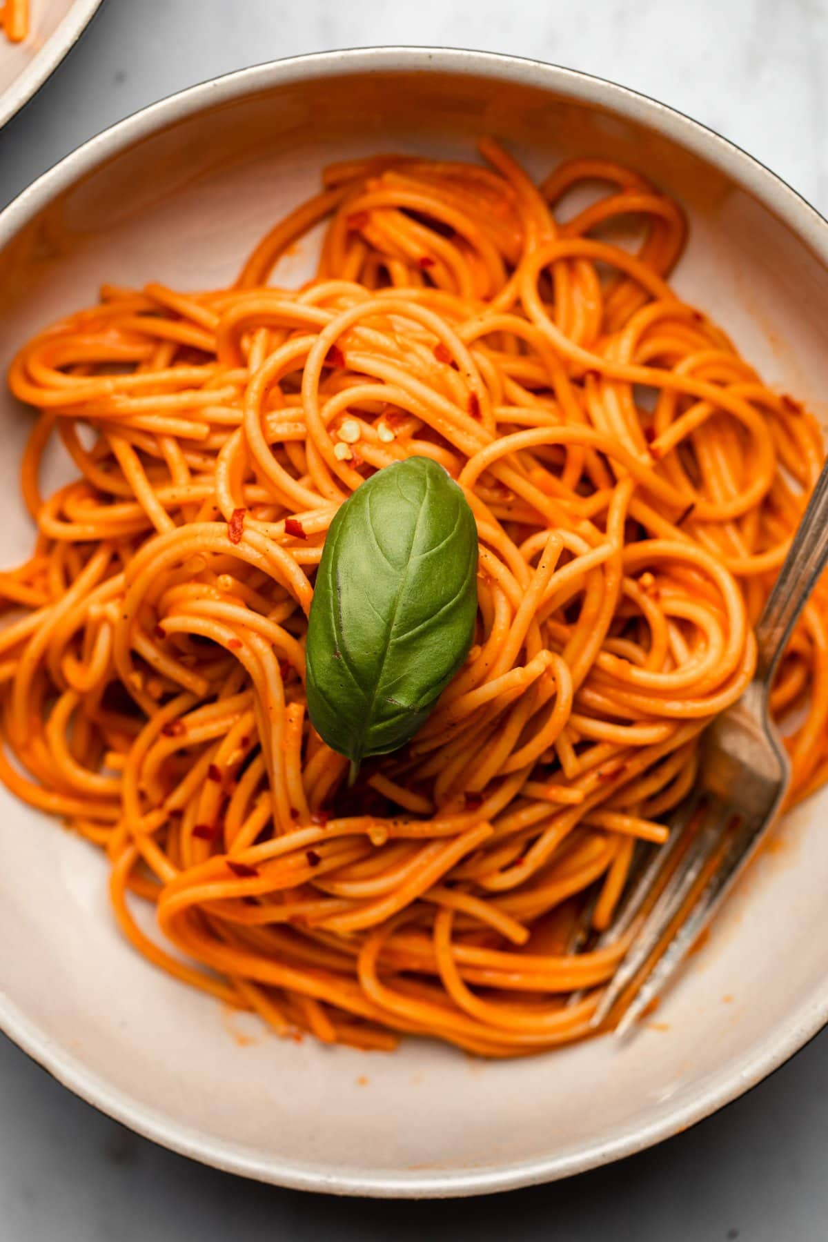 close up photo of spaghetti tossed in red pepper sauce topped with fresh basil