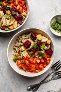 white bowls filled with quinoa, beans, and roasted vegetables on marble background