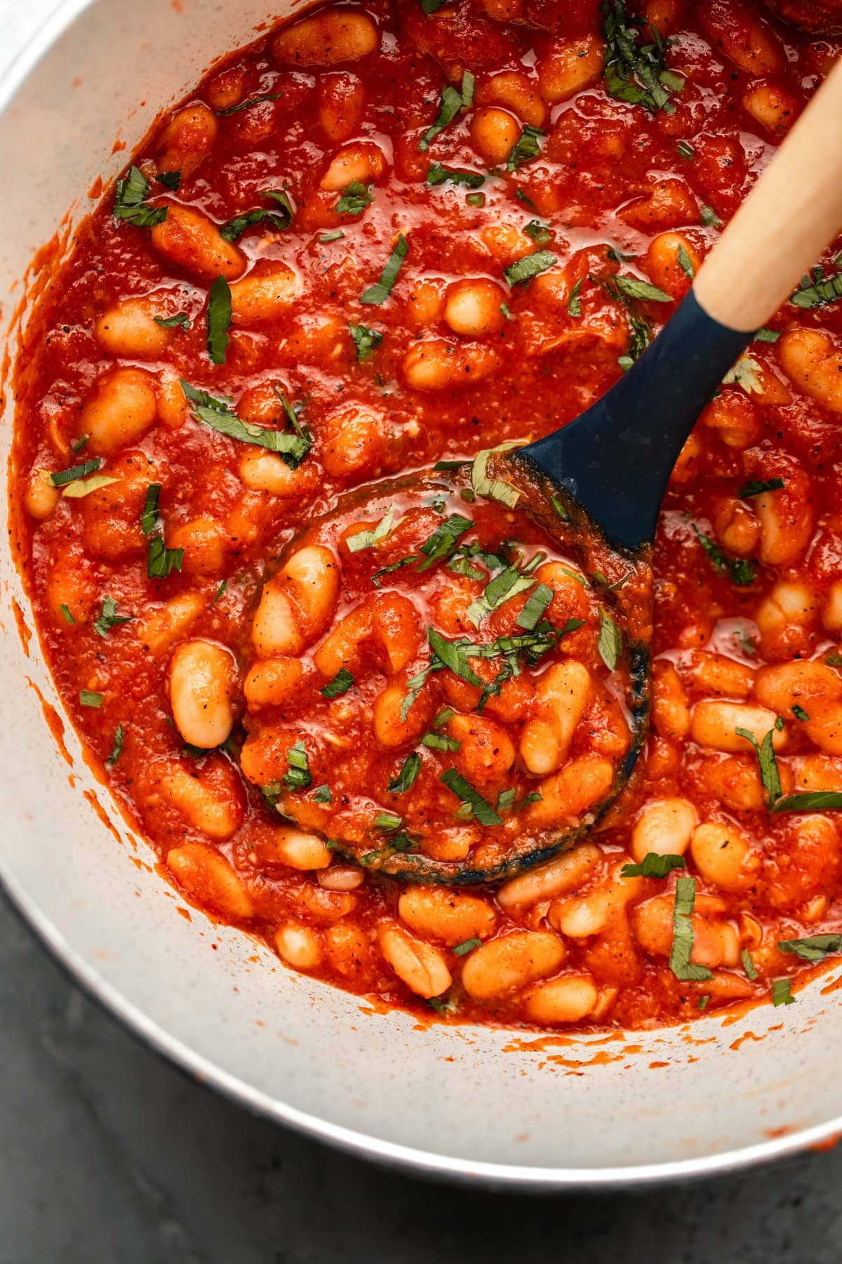white pot of sweet & smoky white beans in red sauce garnished with chopped parsley