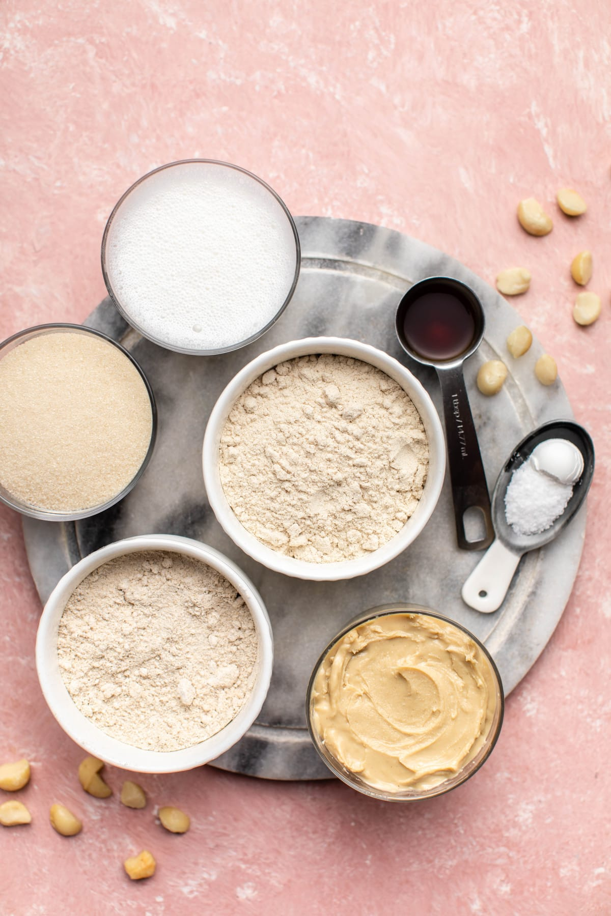 ingredients for cashew butter blondies on marble serving tray and pink background