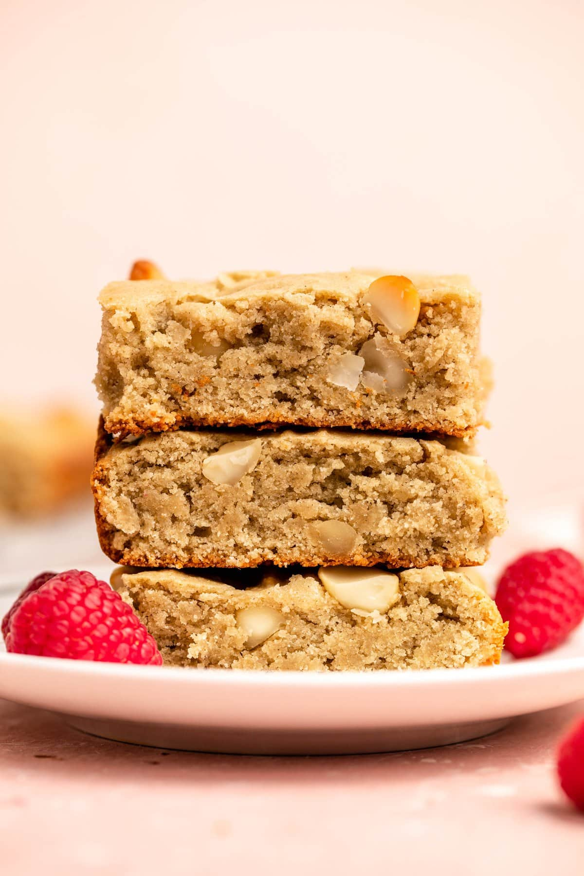 stack of vegan blondies on white plate with raspberries and pink background