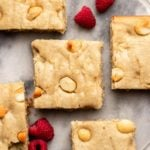 slices of cashew butter blondies on marble background with raspberries