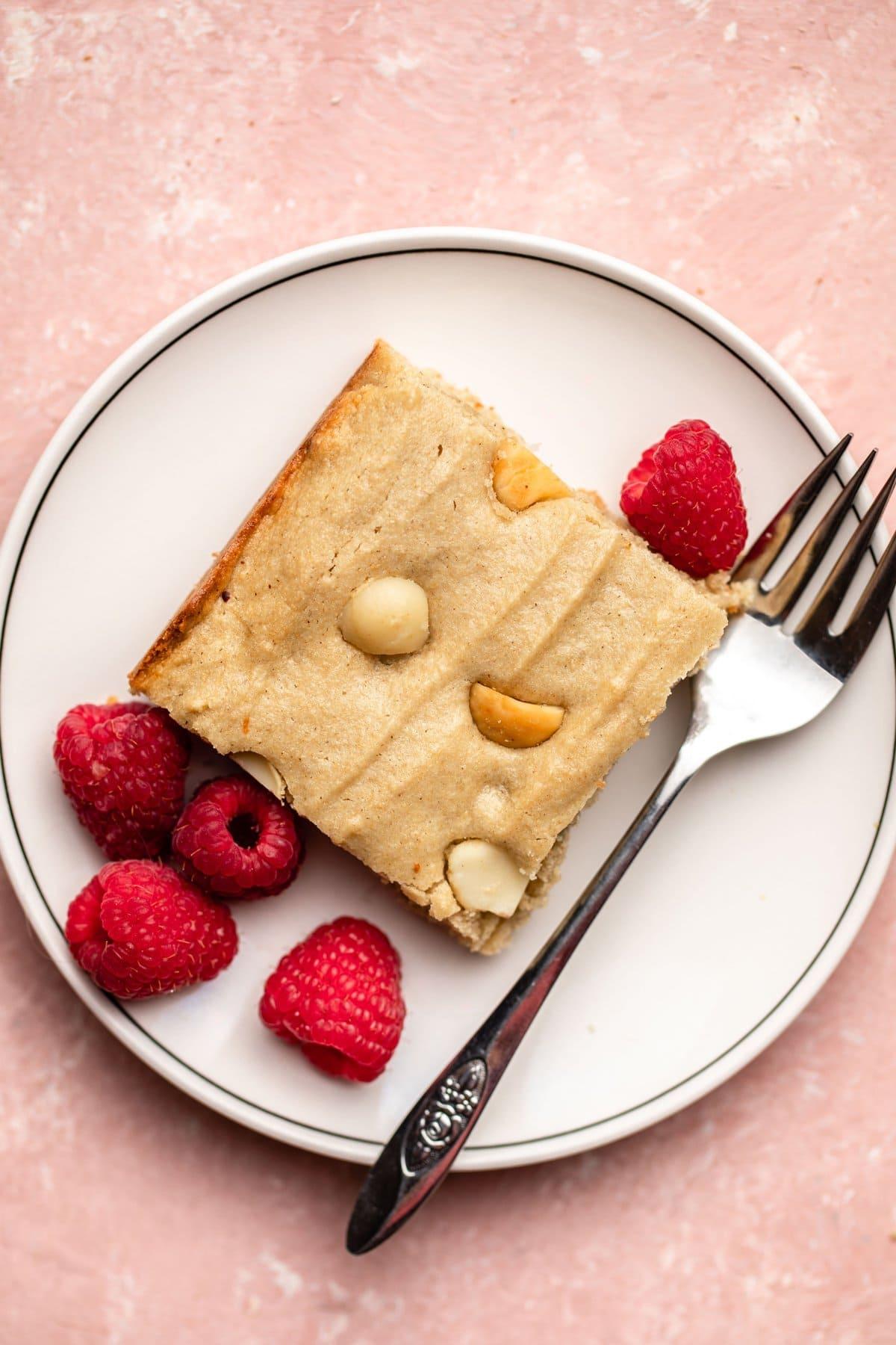 slice of vegan blondie on white plate with raspberries and fork