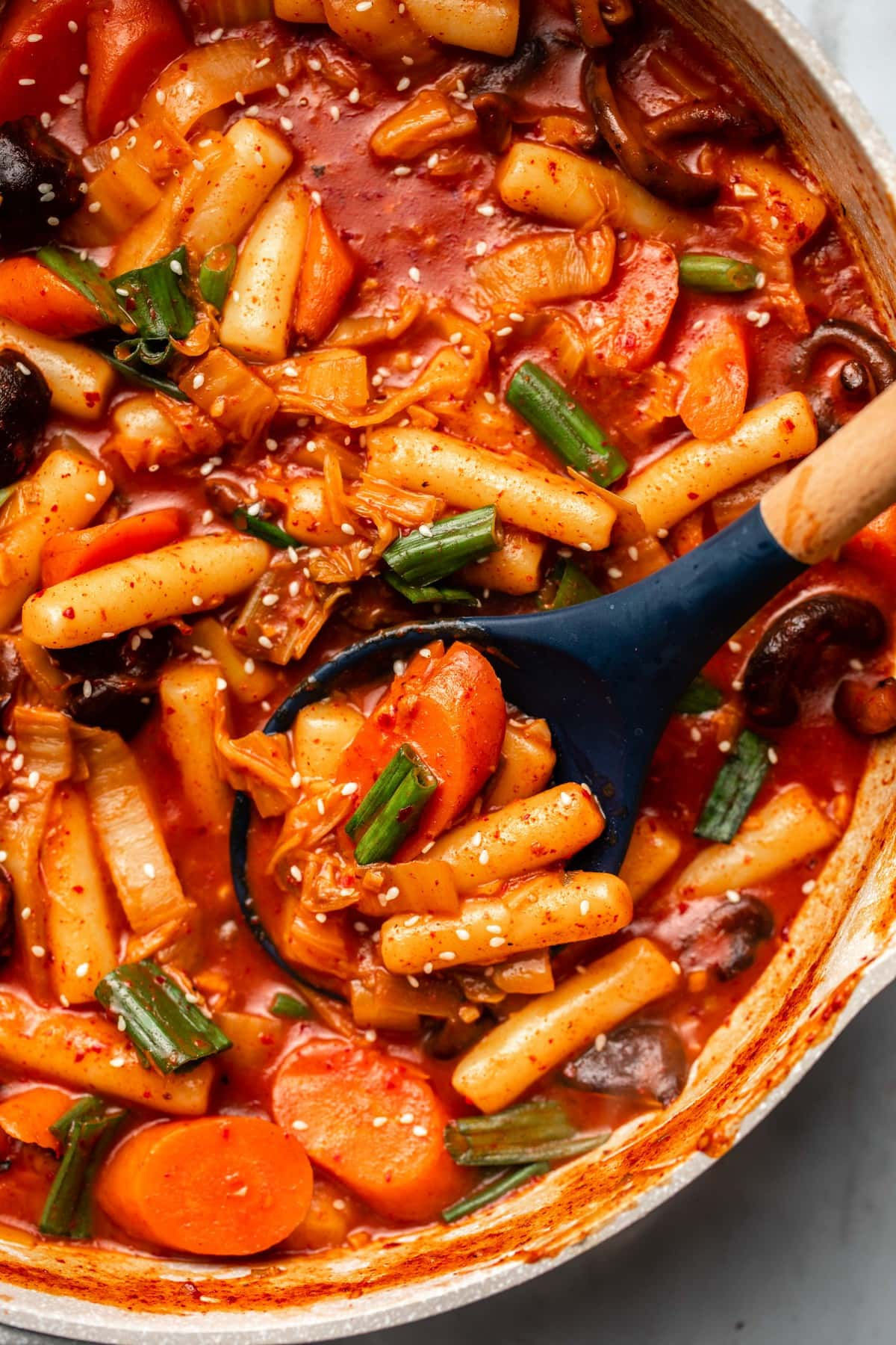 close up photo of cooked tteokbokki with sesame seeds in pot with wooden spoon