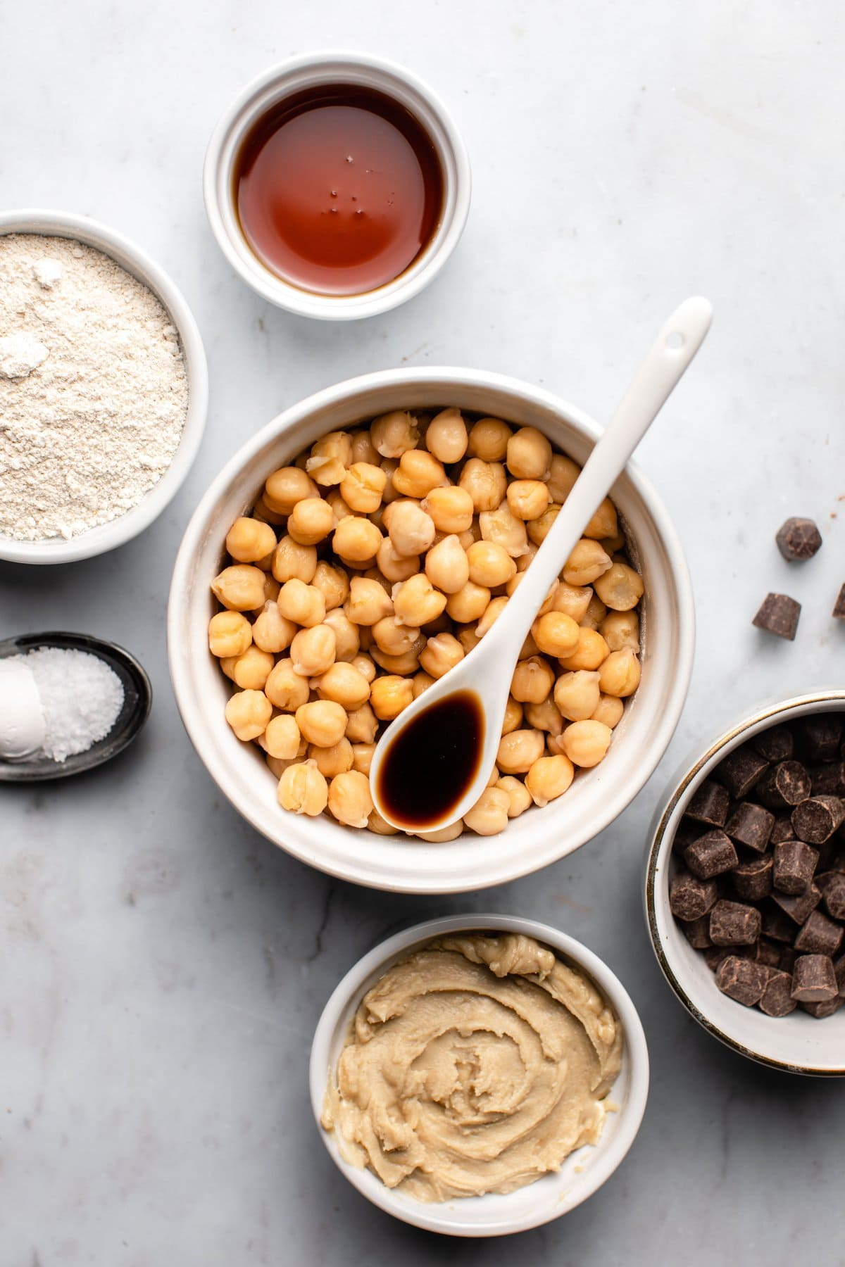 ingredients for chickpea chocolate chip cookies in small bowls on marble background