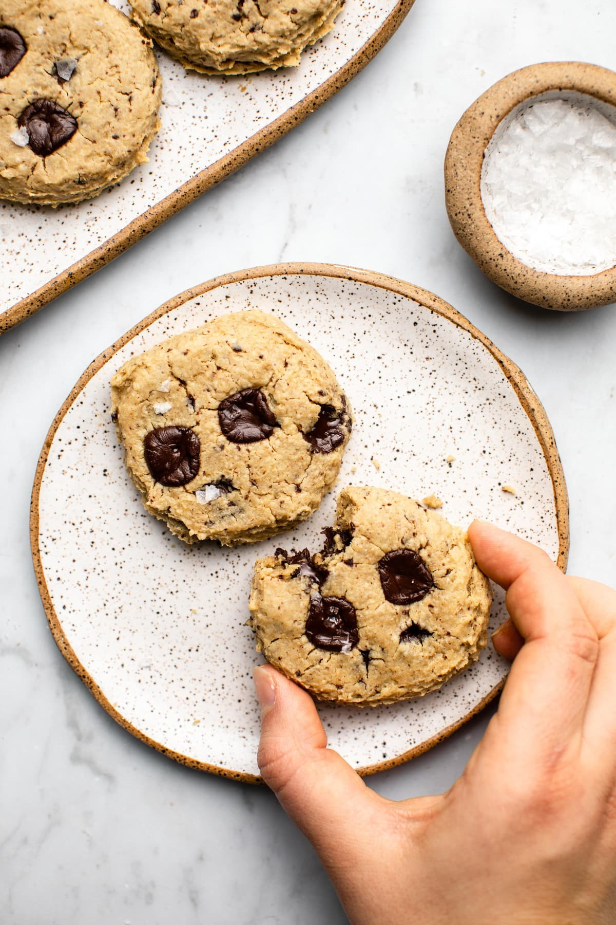 two chocolate chip cookies on white plate with hand grabbing for a cookie on marble background