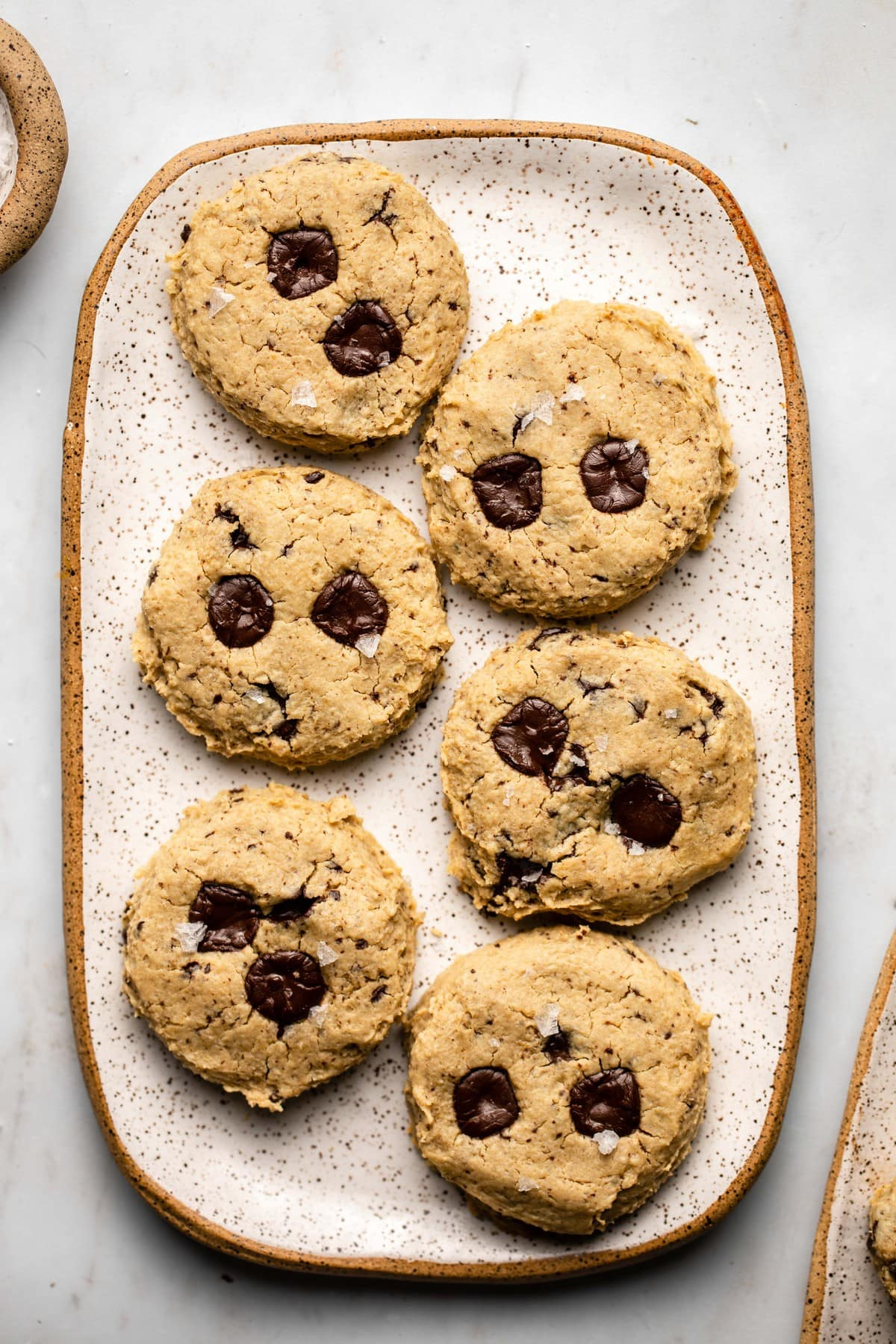 cooked chickpea chocolate chip cookies on white speckled tray on marble background
