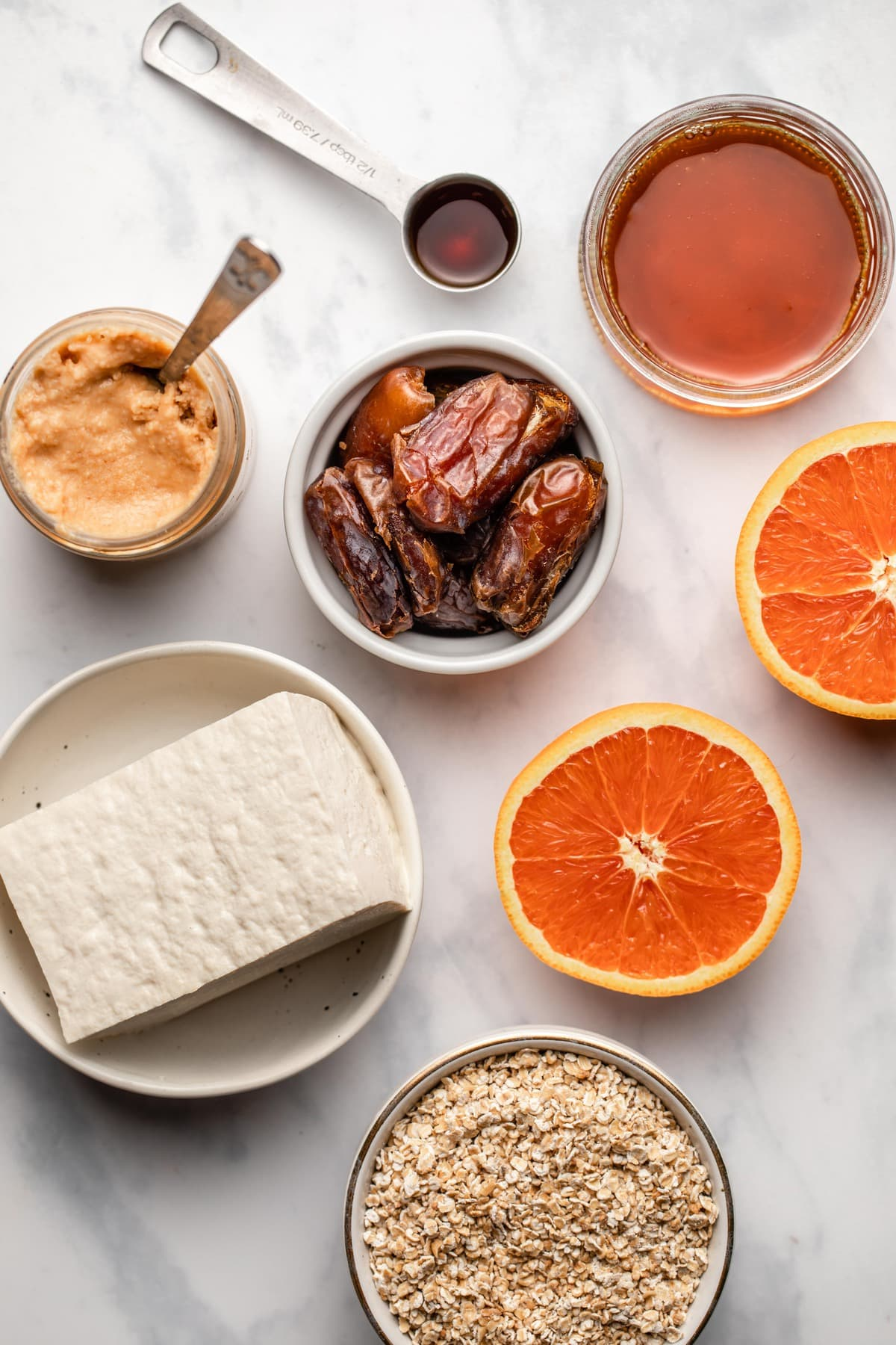 ingredients for toasted coconut cheesecake in small bowls on marble background