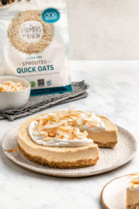 toasted coconut cheesecake on white speckled plate on marble background with bag of one degree organics quick oats in background
