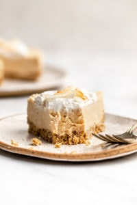 slice of toasted coconut cheesecake with fork bite taken out of it to show texture on marble background